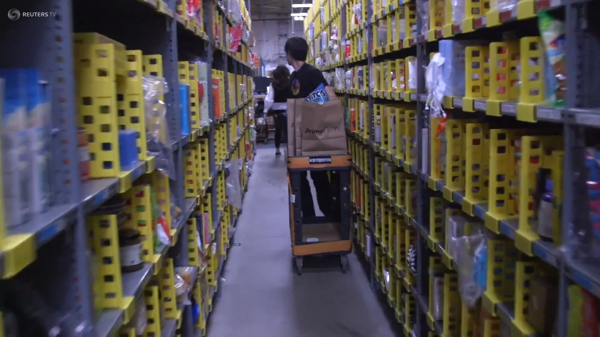 Man running through shelves to fulfill orders.